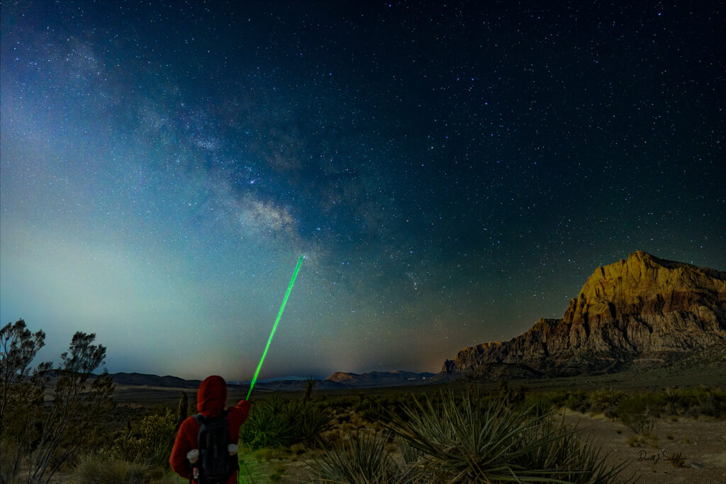 A young man points out the center of the Milky Way Galaxy in Red Rock Canyon State Park, Nevada